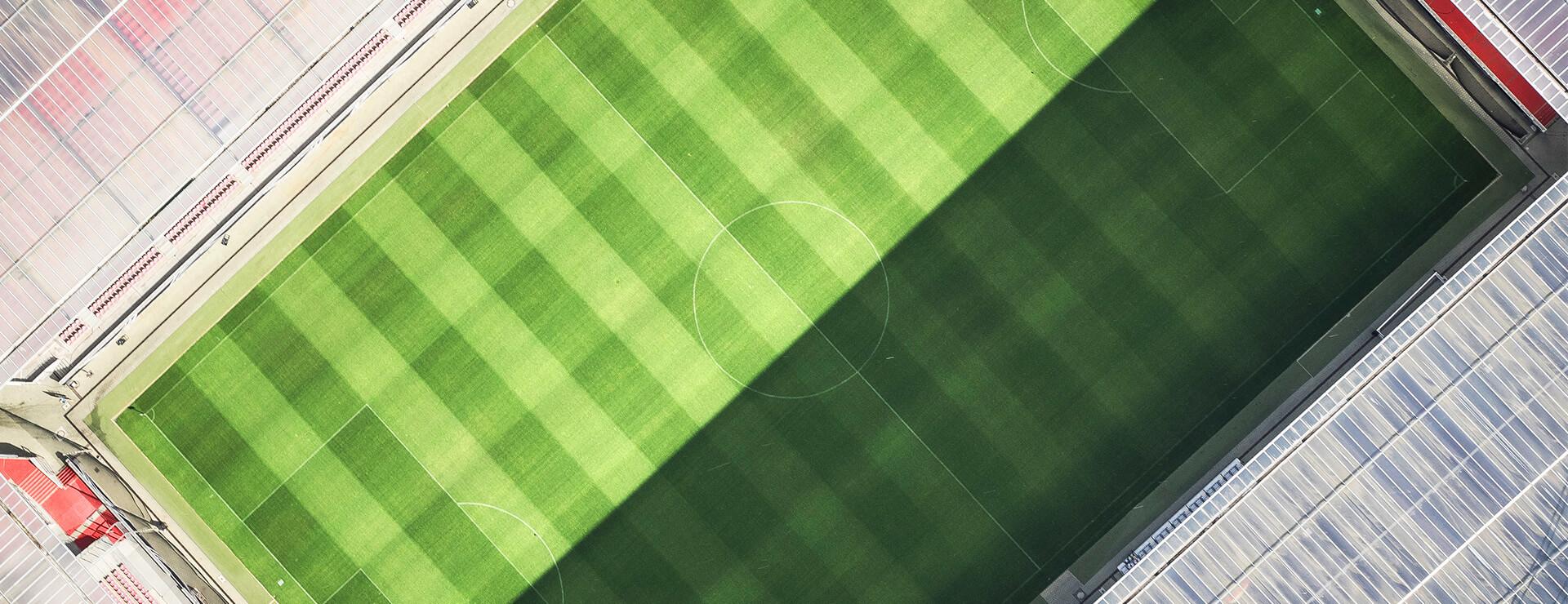 Fußballstadion von oben. Eine Hälfte des Platzes liegt in der Sonne. Die andere Hälfte liegt im Schatten.